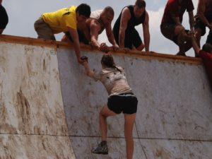 Group of People Helping Woman Finish Climb Up a Wall