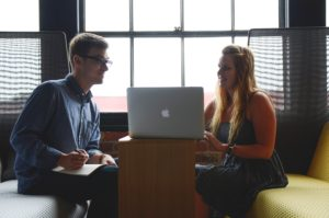 Man and Woman Talking in Front of a Mac Laptop