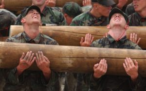 Team of Military Members Carrying Heavy Log Together