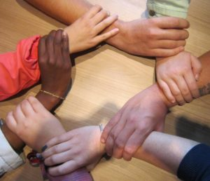 Group of Hands Interlocking Wrists Making a Circle